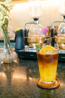 Orange and lemon juice soda topped with black coffee in glass with rosemary and cinnamon