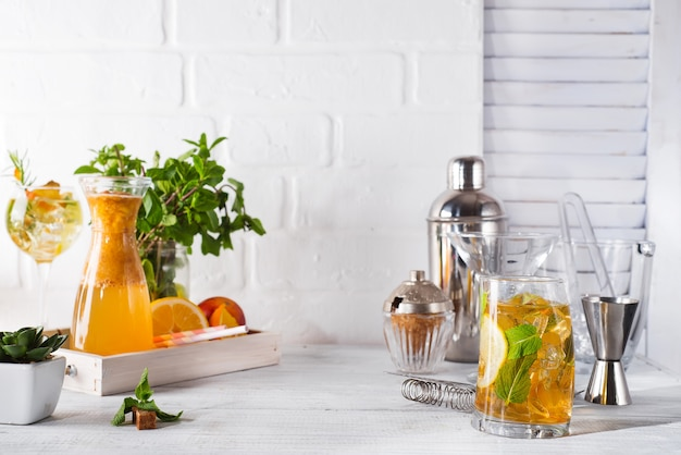 Orange lemonade in the decanter , cocktail glass with ice, mint and ginger