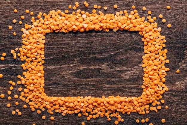 오렌지 렌즈 콩 나무 배경에 멋지게 배치. 평면도. 직사각형 복사 공간. 채식주의 자 음식. 준비되지 않았습니다.