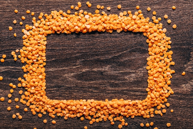Orange lentils nicely laid out on a wooden background. top view. rectangular copy space. vegetarian food. unprepared.