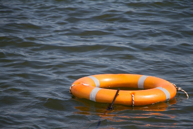 Orange life buoy on water surface as symbol of help and hope, selective focus