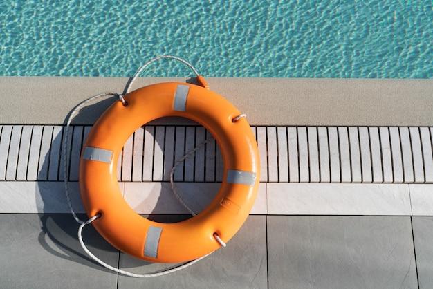 プールサイドのオレンジ色の救命浮環。救命浮環、救助の概念
