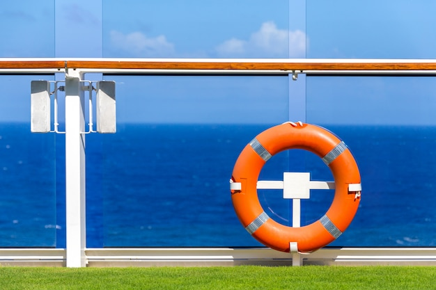 Orange lifebuoy on a deck of cruise ship with ocean on background with blue sky and copy space