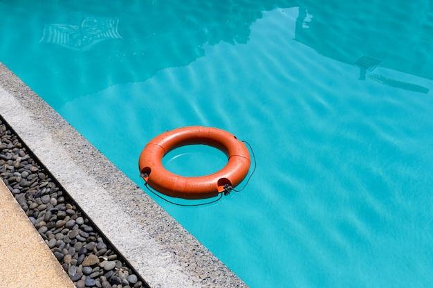 Orange lifebuoy floating on surface swimming pool
