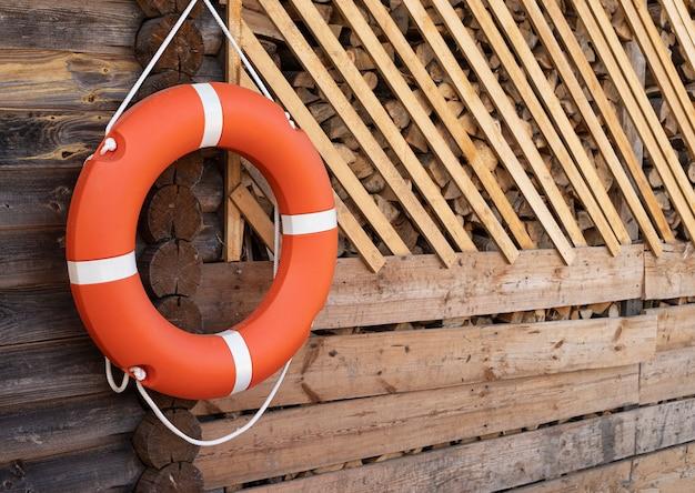 Оранжевый спасательный круг висит на веревке на деревянной стене