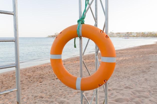 Orange lifebuoy on lifeguard tower on blue sky and beach