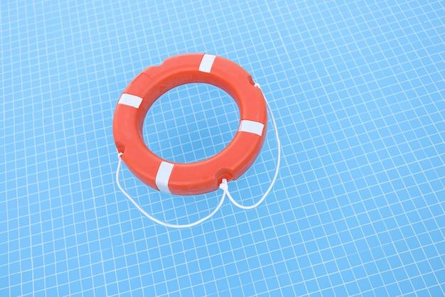 スイミングプールのクローズアップで水の上に横たわっているオレンジ色の救命浮環