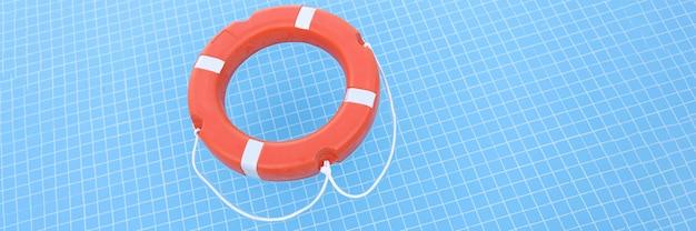 Оранжевый спасательный круг, лежащий на воде в бассейне крупным планом