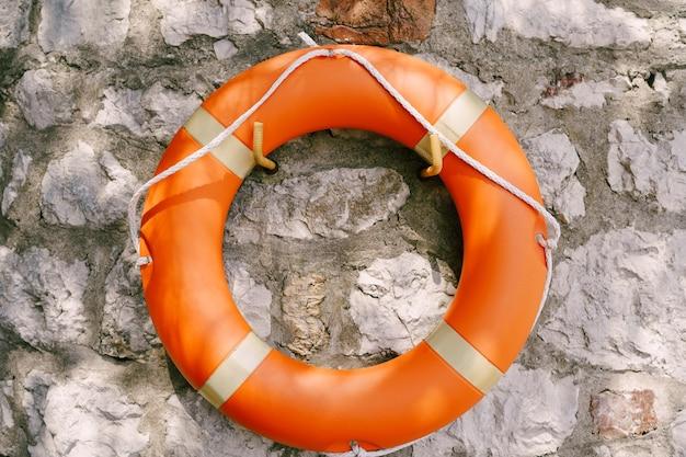 Оранжевый спасательный круг на серой каменной стене.