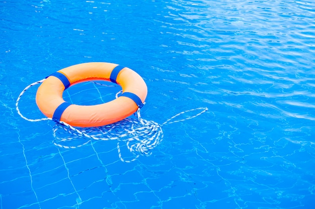 Orange lifebuoy pool ring float on blue water. life ring in swimming pool, life ring floating on top of sunny blue water
