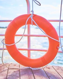 Оранжевый спасательный круг с веревкой на деревянном пирсе у моря. оборудование для спасения утопающих. безопасность людей на пляже и в воде.