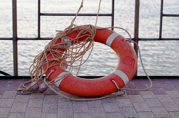 Orange lifebuoy with rope on the pier