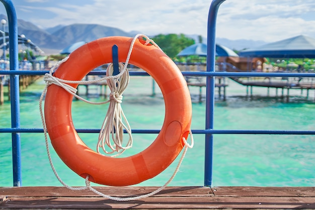 Orange lifebuoy with rope on a wooden pier near sea