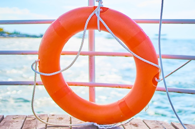 Orange lifebuoy with rope on a wooden pier near sea.