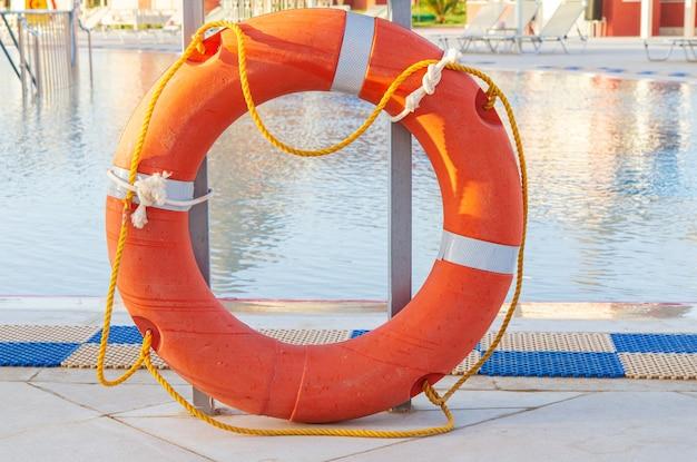 Оранжевый спасательный круг с веревками на кафельном полу возле бассейна