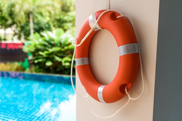 Orange lifebuoy with white strips hanging on the wall near pool, has space on left side for creative