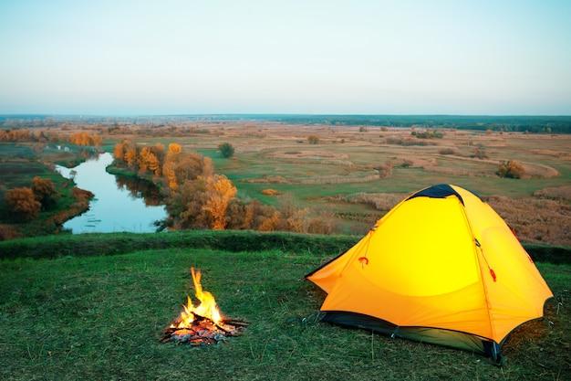 Палатка и костер с оранжевой подсветкой на холме над рекой