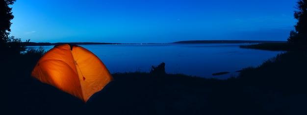 Палатка с оранжевым освещением на озере