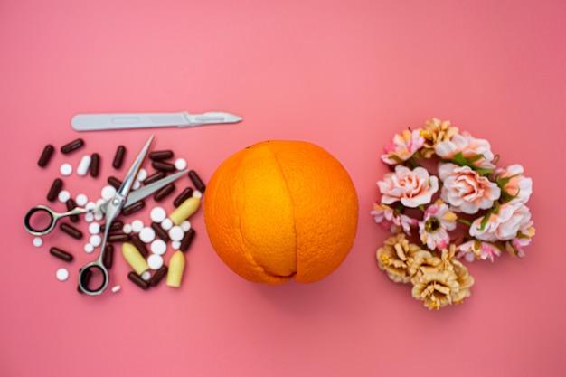 질, 메스, 가위, 분홍색 배경에 꽃과 같은 오렌지. 부인과 질환의 예방 및 치료 개념.