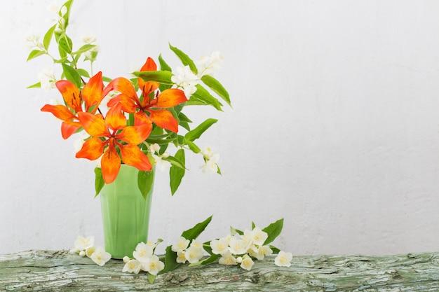 Оранжевая лилия в вазе на белом фоне