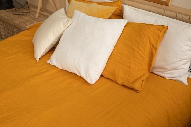 オレンジのリネンベッドリネン、白とオレンジの枕。快適で居心地の良い家