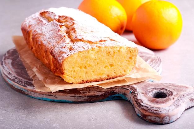 Orange loaf cake sliced on board, selective focus