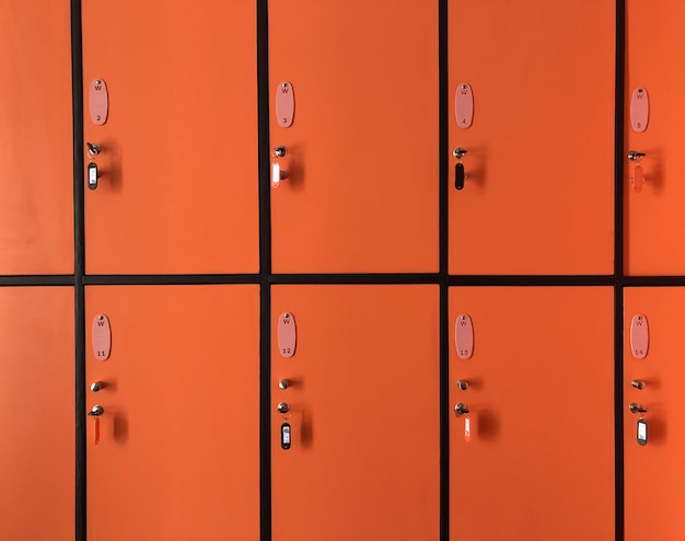 The orange  lockers in gym have many doors locked with keys for private safety