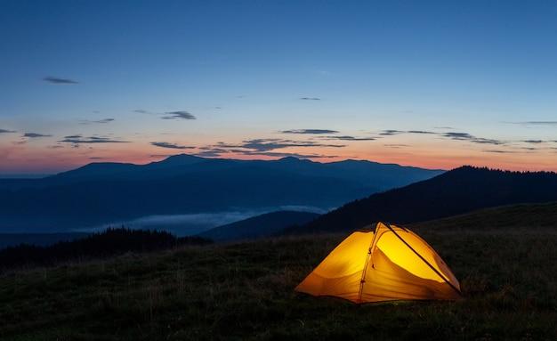 Оранжевая светящаяся палатка на горе вечером или ранним утром