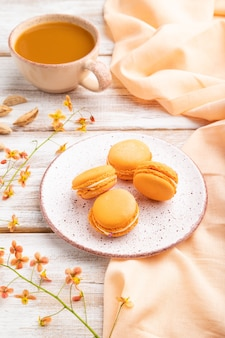 Orange macarons or macaroons cakes with cup of apricot juice on a white wooden background and orange linen textile.