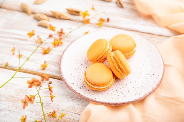 Orange macarons or macaroons cakes with cup of apricot juice on a white wooden background and orange linen textile