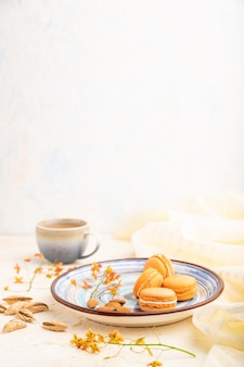 Orange macarons or macaroons cakes with cup of coffee on a white concrete background and linen textile.