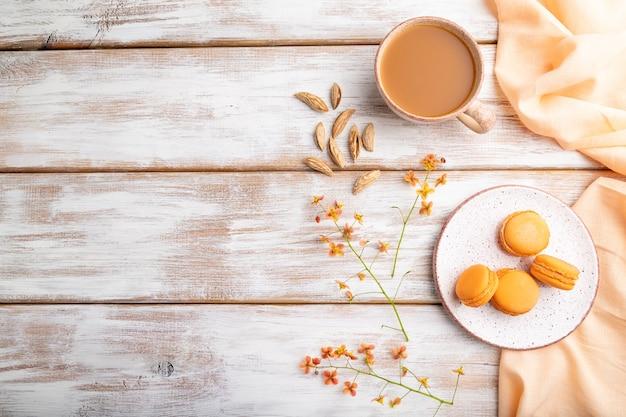 白い木製のテーブルとオレンジ色のリネン繊維にアプリコットジュースのカップとオレンジのマカロンまたはマカロンケーキ。トップビュー、フラットレイアウト、コピースペース。