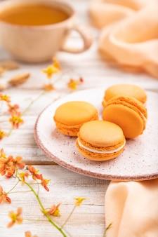Апельсиновые макароны или пирожные с макаронами с чашкой абрикосового сока