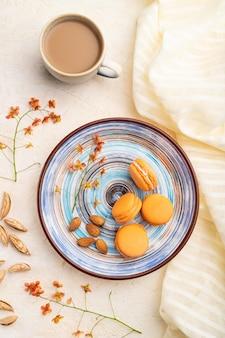 白いコンクリートのテーブルとリネンの繊維にコーヒーのカップとオレンジのマカロンやマカロンのケーキ。トップビュー、フラット横たわっていた、クローズアップ。