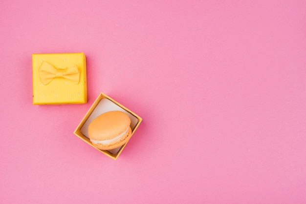 Orange macaroon in yellow gift-box with copy-space
