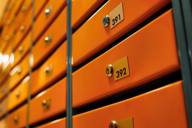 Оранжевые почтовые ящики в многоквартирном жилом доме. четные ряды пронумерованных почтовых ящиков. концепция переписки в городе. вы можете использовать его в качестве фона для своего объявления. копировать пространство