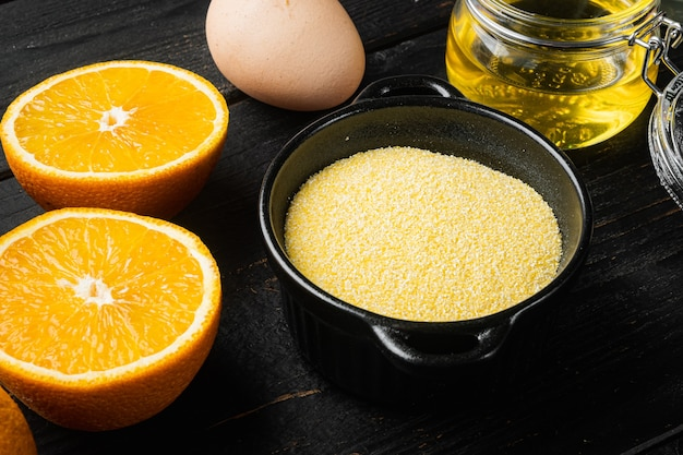 Orange and mandarin cake with polenta ingredients, with eggs and honey set, on black wooden table background