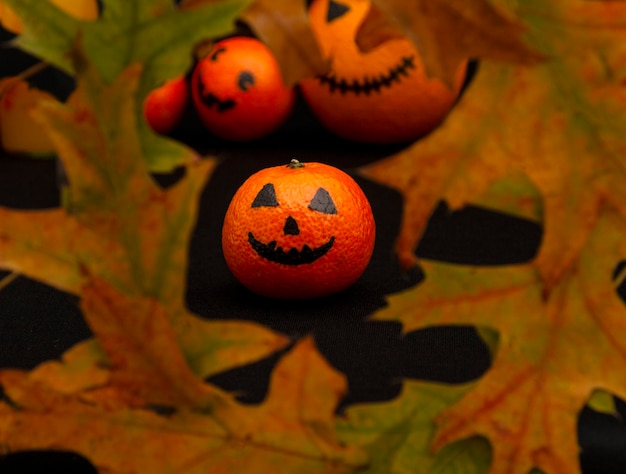 オレンジ色のマンダリンは、葉の幸せなハロウィーンの柑橘類のハロウィーンのカボチャのように描かれました