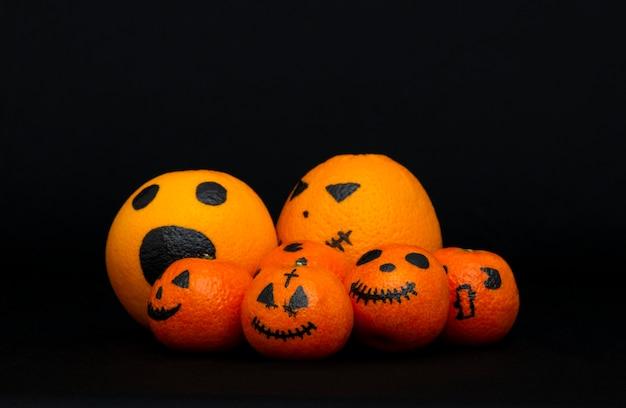Оранжевые мандарины, нарисованные как тыква на хэллоуин