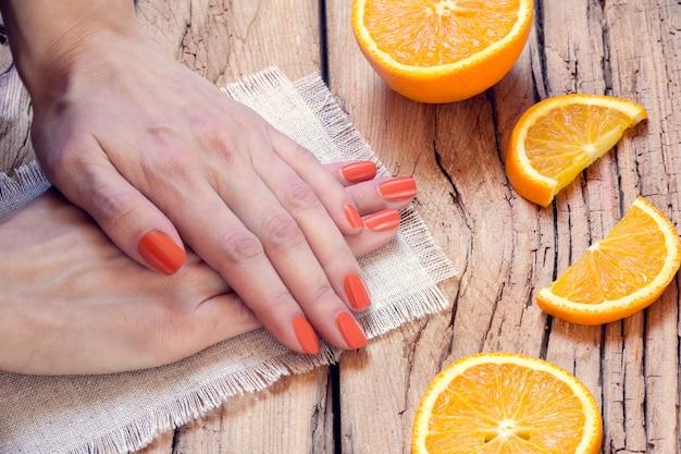 オレンジ色のマニキュアとオレンジ