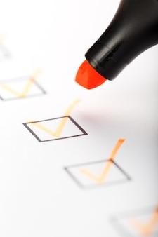 Оранжевый маркер с маркерами на листе контрольного списка