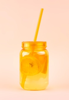 Orange mason jar of lemonade with lemons and ice and straw on a soft coral.