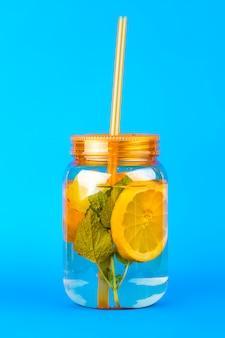 Orange mason jar of lemonade with lemons, mint, ice and straw on a vivid blue
