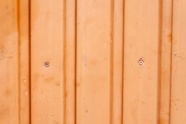 縦の波形の縞模様のオレンジ色の金属柵