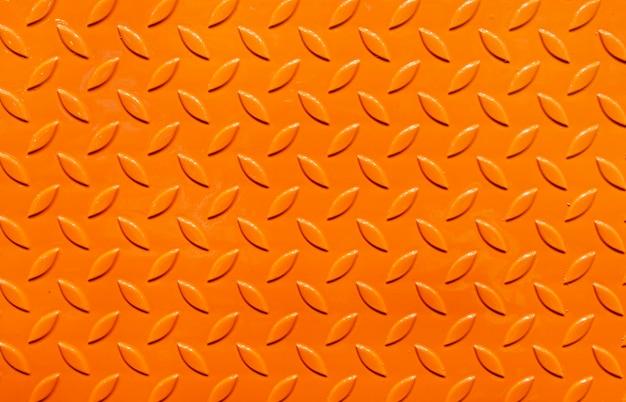 オレンジ色の金属板の質感、ステンレスまたは金属の質感の背景