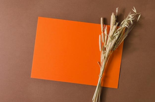 茶色の背景にオレンジ色のモックアップ。オレンジ色の葉に乾燥ハーブの秋の花束。フラットレイ、テキストのコピー
