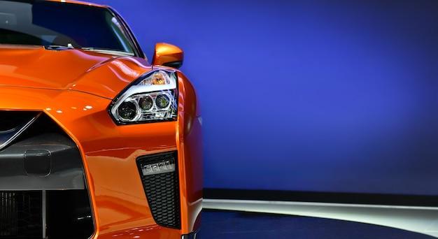 Оранжевые фары современного автомобиля на синем фоне копией пространства