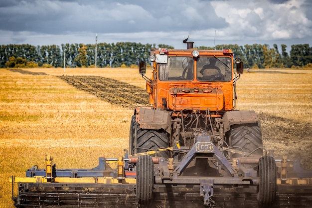 An orange modern tractor plows the earth inâ a golden field of wheat on a summer day