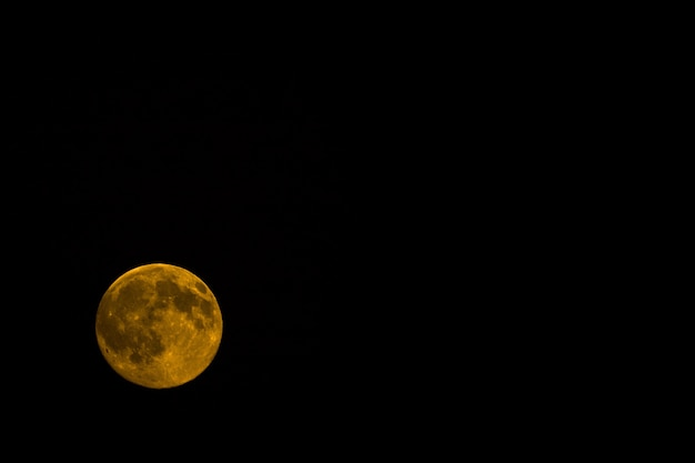 Orange moon at night isolated on a black