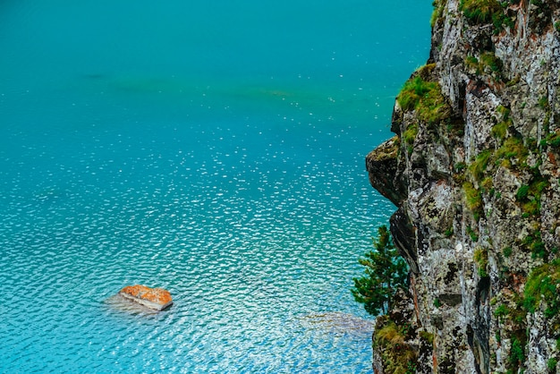 Orange mossy stone in azure mountain lake near large cliff with rich vegetation